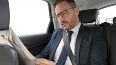 Businessman in taxi cab reading newspaper Stock Footage