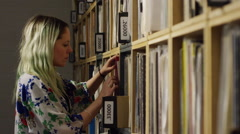 Young woman shopping for vinyl records in music store Stock Footage