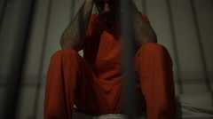Dramatic scene of a depressed inmate in jail - stock footage