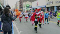 Spectators cheering costumed runners racing in the TCS New York City Marathon. Stock Footage