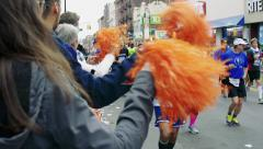 Spectators cheering runners racing in marathon. Stock Footage