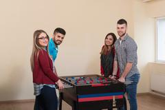 Group Of Friends Playing Soccer Table Foosball Stock Photos