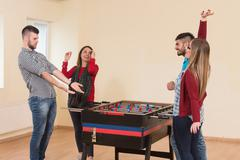 Friends Playing Soccer Table - Foosball Stock Photos