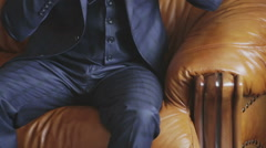 Attractive young man in a suit sitting on a retro couch Stock Footage