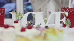Decor wedding ceremony word love on the bank on the background of flowers - stock footage