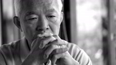 video of Asian senior guy with hand on face thinking, worry and sad - stock footage