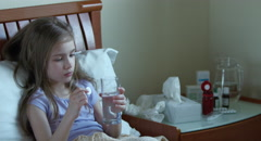 Sick child girl 7 years old sitting on the bed. Girl throws an aspirin tablet Stock Footage