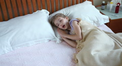 Sick girl 7 years old sneezing and coughs and lying on the bed. Panning Stock Footage