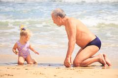 Grandpa Little Girl Sit on Wet Sand Look at Shell by Surf - stock photo