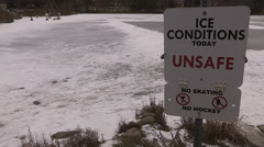 Dangerous unsafe thin ice warning signs at pond - stock footage