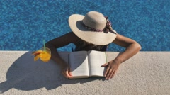 Woman reading by the pool from above Stock Footage