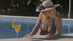 Woman reading relaxing by  swimming pool Stock Footage