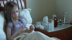 Sick girl 7 years old sitting on the bed under the blanket Stock Footage