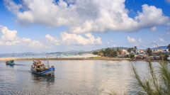 Fishing Boat Drifts to Shore in Bay Resort City Hills Sky Stock Footage