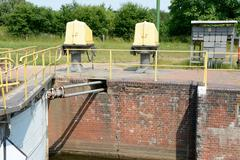 Part of old sluice gate and electric devices on embankment - stock photo