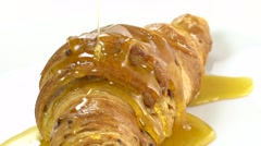 Pouring honey on croissant, Croissant with honey, rotating, slow - stock footage