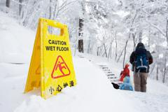 Warning caution sign board on snow floor on hill Stock Photos