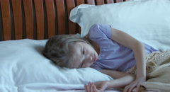 Portrait sick girl 7 years old lying on a bed. Girl measures the temperature Stock Footage