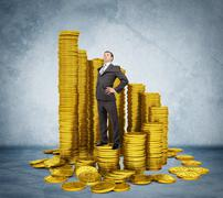 Proud businessman standing on stack of coins - stock photo