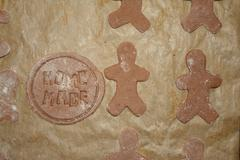 Human and round shape gingerbreads on brow paper during preparation. Home mad Stock Photos