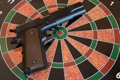 Airsoft gun on target - dartboard - stock photo