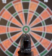 Airsoft gun aiming at target - dartboard - stock photo