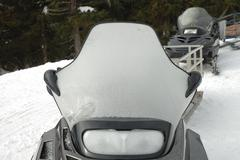 Frosted snowmobile windshield and headlight. Stock Photos