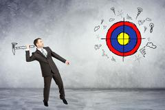 Businessman throwing axe to darts - stock photo