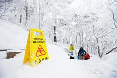 Warning caution sign board on snow floor on hill Stock Photos