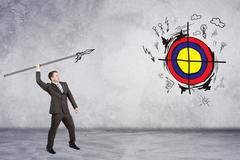 Businessman throwing spear to darts - stock photo