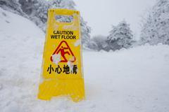 Warning caution sign board on snow floor on hill Kuvituskuvat