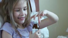 Closeup portrait sick child girl 7 years old takes vitamins without asking Stock Footage