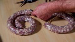Cutting extra intestine off sausage - stock footage