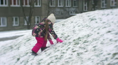 Little Girl With Braid is Climbing up to a Hill Feet Slide by Snow Walking on a Stock Footage
