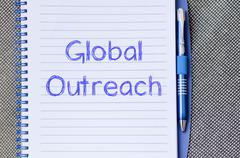 Global outreach write on notebook - stock photo