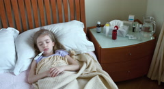 Portrait girl child 7 years old lying on a bed is sick Stock Footage