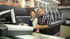 Man working with apprentice in printing house Stock Footage