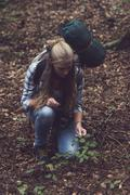 Backpacking woman touching shrub on forest ground. - stock photo