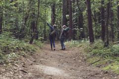 Two women hiking in forest pointing at tree. Kuvituskuvat