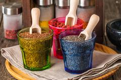 Seeds and goji in a wooden spoons - stock photo