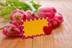 Pink tulips with heart card on wood background. - stock photo