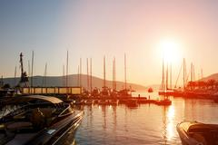 Yachts and boats at Adriatic sea bay at sunset in golden and pink tones. - stock photo
