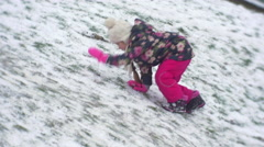 Little Girl With Braid is Climbing up the Hill Feet Slide by Snow Raising up Stock Footage