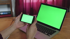 Girl Holding a green screen iphone and macbook pro Stock Footage