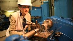 Metal worker woman using machine in workshop - stock footage