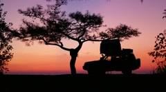 Silhouette of car with mounted tent on the roof at sunrise sunset Stock Footage