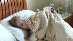 Coughing girl lying on a bed under the blanket. Portrait sick girl 7 years old Stock Footage