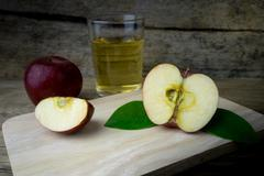 Apple juice and apples on a wooden table - stock photo