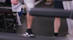 4K Man with prosthetic leg working out at the gym with personal trainer Stock Footage