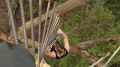 Girl climbs up a 75m high tree Stock Footage